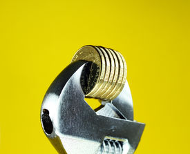picture of budge  - A stack of Gold Dollar Coins being squeezed in a silver adjustable spanner - JPG