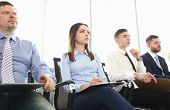 Portrait Of Gorgeous Woman And Men Sitting In Modern Conference Room And Discussing Important Busine poster