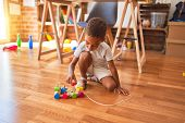 Beautiful african american toddler playing with wooden blocks train toy around lots of toys at kinde poster