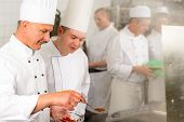 stock photo of canteen  - Professional kitchen chef cook add spice paprika prepare food meals - JPG