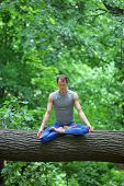 caucasian male meditating in forest - yoga asana on tree trunk poster