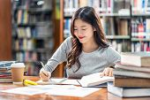 Asian Young Student In Casual Suit Reading And Doing Homework In Library Of University Or Colleage W poster