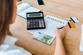 Selective Focus Of Woman Signing Document With Bankruptcy Letters Near Credit Cards And Calculator poster