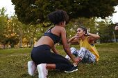 Fit Young Woman Doing Crunches Exercise With Her Female Friends During Athlete Workout In The Park - poster