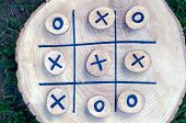 Tic Tac Toe Game On A Wooden Board With Wooden Tac Toe And Crosses. Winner Strategy, Winning Skill,  poster