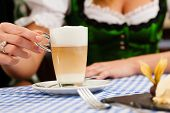 Young woman in traditional Bavarian Tracht in restaurant or pub eating dessert and drinking coffee, close-up