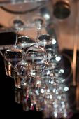 Photo Of Lots Of Wine Glasses Hanging Upside Down. Wineglasses Dry. Selective Focus, Blurred Backgro poster