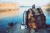Enameled Mug Of Coffee Or Tea, Backpack Of Traveller And Thermos On Wooden Pier On Tranquil Lake. poster