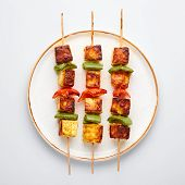 Paneer Tikka At Skewers In White Plate Isolated At White Background. Paneer Tikka Is An Indian Cuisi poster