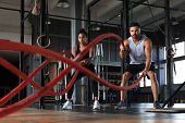 Athletic Young Couple With Battle Rope Doing Exercise In Functional Training Fitness Gym. poster