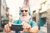 Senior Bearded Man Taking Selfie With Mobile Phone While Listening Favorite Playlist With Headphones poster