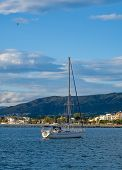 Sailing Yacht, Sailboat In The Bay On City Landscape And Cloudy Blue Sky Background. The Boat Is Anc poster