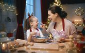 Merry Christmas and Happy Holidays. Family preparation holiday food. Mother and daughter cooking coo poster