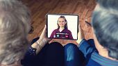 Senior Couple At Home Holding Digital Tablet During Video Call With Family Doctor - Virtual Live Con poster
