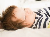 Sleeping Baby On Parents Bed. 0-1 Year Old Baby. Portrait Of A Newborn In The Parents Bed. Babys Day poster