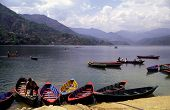 A scenic view of country of Nepal showing boats moored on Phewa Lake.