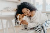 Lovely Young Curly African American Woman Embraces Beloved Pedigree Dog With Love, Has Gentle Smile, poster