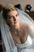 Portrait of auburn haired bride in tiara on wedding day.