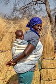 African woman in the village carrying her child in the back, wrapped in a blanket poster