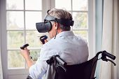 Mature Disabled Man In Wheelchair At Home Wearing Virtual Reality Headset Holding Gaming Controllers poster