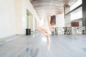 Charming Female Dancer Tiptoeing While Performing Gracefully On Urban Scene poster