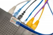 stock photo of cat5  - Close macro focus on internet lan cat5 cables as concept for cyberwarfare - JPG