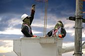 stock photo of lineman  - Electricians on a crane - JPG