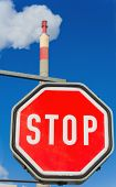 chimney of an industrial enterprise and stop sign. symbolic photo for environmental protection and o