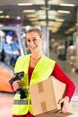Female worker with protective vest and scanner, holds package, standing at warehouse of freight forw