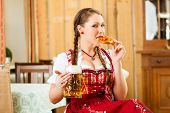 stock photo of stein  - Young woman in traditional Bavarian Tracht in restaurant or pub with beer and steins and pretzel - JPG