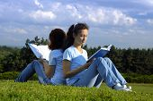 Two girls sitting on grass studying in the nature reading books outside