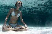 Underwater portrait of a young lady holding a breath on a sandy bottom in a yogic lotus position