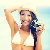 Beach woman with vintage retro camera having fun playful laughing in bikini on blue ocean background wearing beach hat. Multicultural Asian / Caucasian girl.