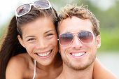 Happy young beach couple closeup portrait outdoors in sun. Young people wearing sunglasses eyewear.
