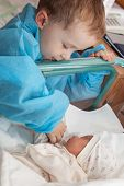 foto of lactating  - The boy looks at his newborn sister in the maternity hospital - JPG