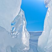 Narrow icy glacier crevasse with snow and blue sky