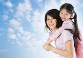 Asian family outdoor fun. Asian mother piggyback her daughter at a nice summer outdoor