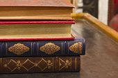 stock photo of annal  - Antique Books with Gold Inlay Stacked on a Table - JPG