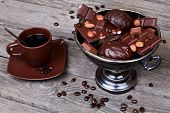 Vase With Chocolate, Nuts And Coffee On A Gray Wooden Background