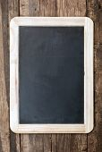 Vintage chalkboard hanging on old wooden background