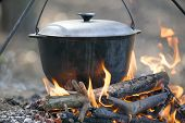 stock photo of stew  - Camping kettle over burning campfire in forest - JPG
