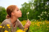 The Girl Blows On  Dandelion On  Background Of A Grass