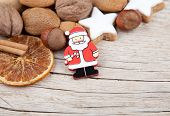 Santa Claus with nuts, oranges and cookies at the edge of wood