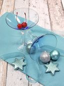 Festive Spirit Blue Martini Cocktai Glasses With Red Maraschino Cherries And Christmas Baubles On A