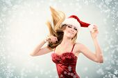 Beautiful cheerful fashion christmas girl dancing in party in Santa's hat in snow, toned