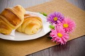 stock photo of croissant  - Closeup of croissants with orange juice with flowers on wooden table - JPG