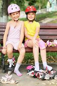 Two girls sitting on the bench and put on rollers and protective knee and elbow pads