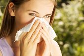 pic of hay fever  - Attractive young woman outdoor with white tissue - JPG