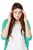 Young casual woman is having headache. Isolated on white.