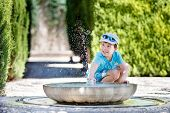 Boy having fun with fountain shot during summer time